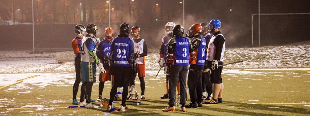 Lacrosse Training im Winter: der Trainer gibt den Herren Anweisungen für die nächste Übung